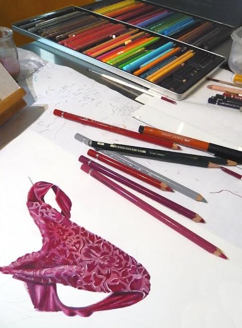 Table de l'atelier avec le dessin en cours de réalisation entouré de crayons divers.