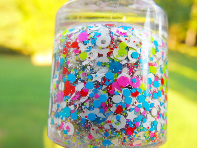 RAINBOW UNICORN- a clear base filled with rainbow colored hex in different colors, white stars, white donuts, white hearts, white bows, and lots of white micro glitter.