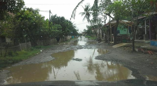 Jalan desa muara tergenang saat musim hujan