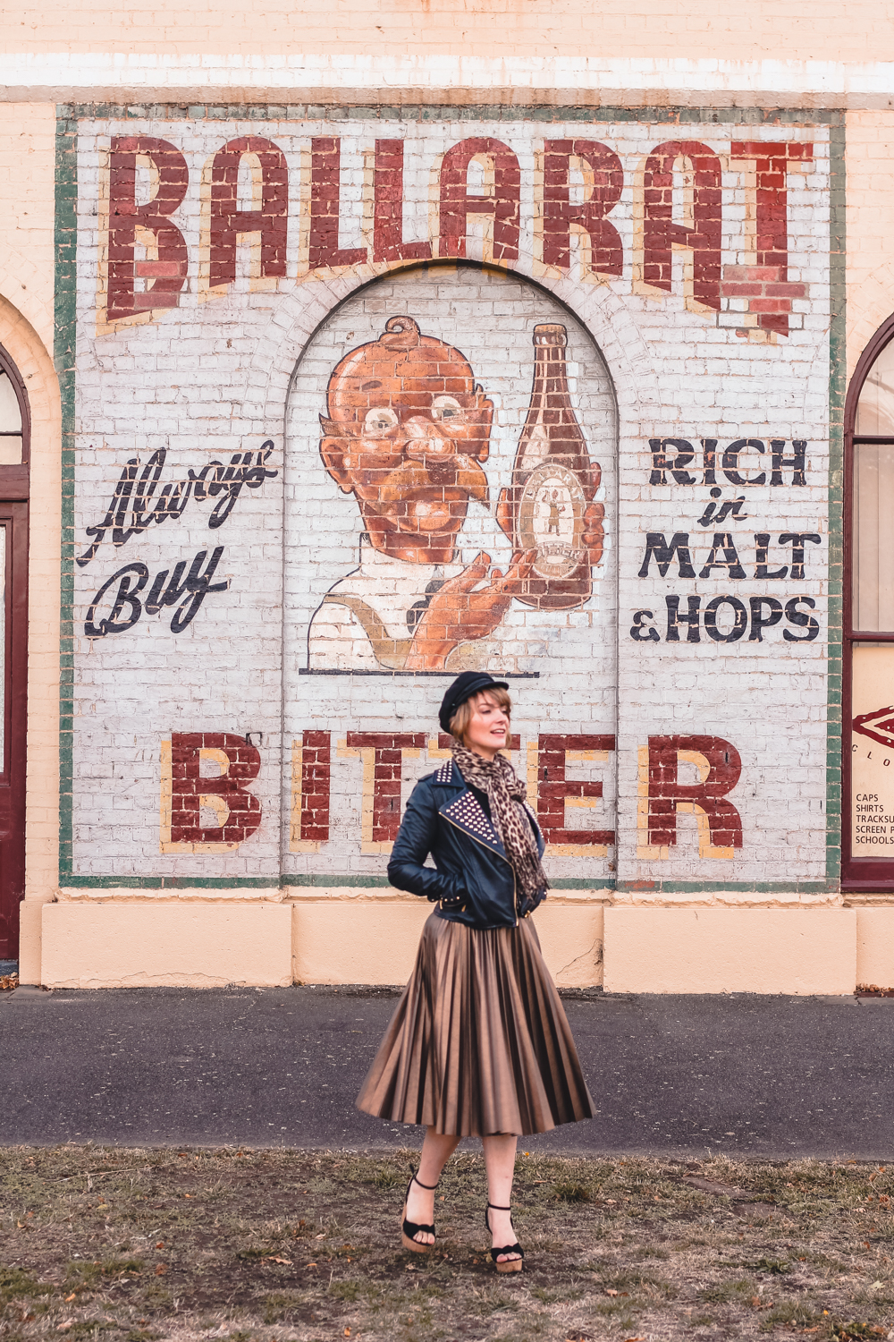 Liana of @findingfemme wearing ASOS pleated skirt at the site of an historic Ballarat Bitter mural
