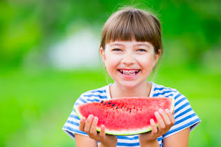 Little girl with braces enjoying a slice of watermelon