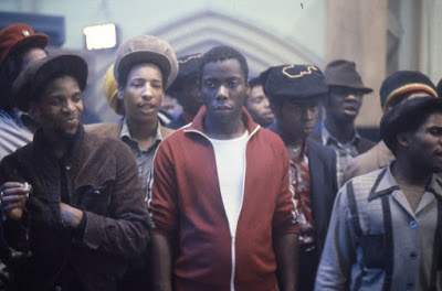 "This is a film still from the movie ""Babylon."" Jah Shaka and the actors portraying Beefy and Lover are in a crown at a sound clash."