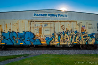 Photograph of a potato processing plant with railroad car in front and sunburst in Aberdeen Idaho by Cramer Imaging