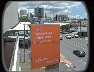 A billboard with the following text: The lift shuddered and stalled, alarm button broken. #8WordStory. @AlexFairhill