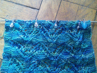A large lace and cables swatch knit in blue-green fingering-weight yarn, knit on a straight needle. There are various stitch markers visible on the needle