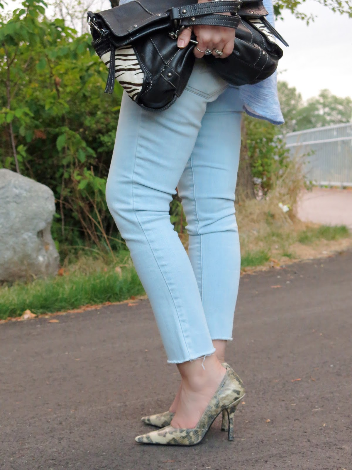 light-wash skinny jeans, snake-print pumps, and zebra-striped bag