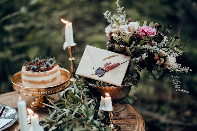 Ozdoby na stoł weselny, złote patery, złote świeczniki, girlandy z liści, szare talerze, piękna papeteria ślubna od White Letters.