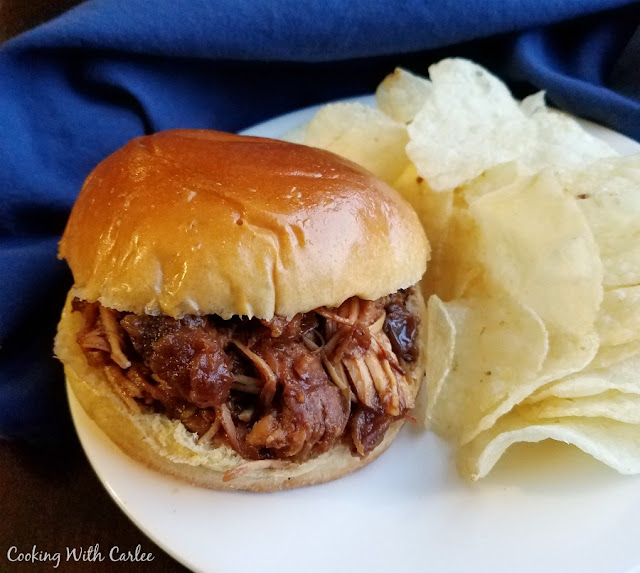 close up of saucy pulled chicken sandwich and potato chips