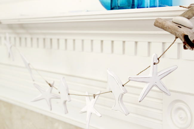 fish and starfish garland on summer mantel with driftwood