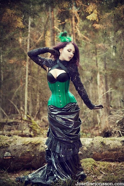 Women's steampunk clothing in bright colors. Green corset with black fishtail hobble skirt and fascinator.