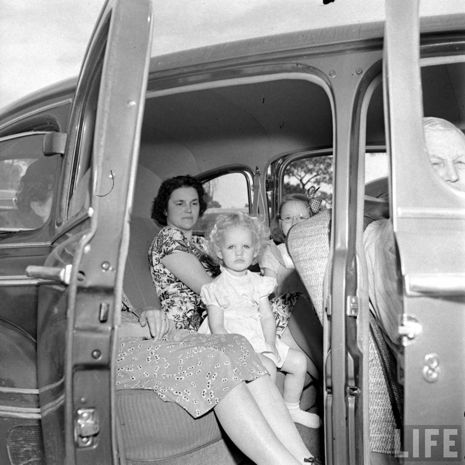 A family being comfortable in their own car while attending the church.