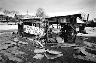 "A black and white photograph of the trashed shanties. A banner reading ""Racists did this"" has been hung on the wreckage."