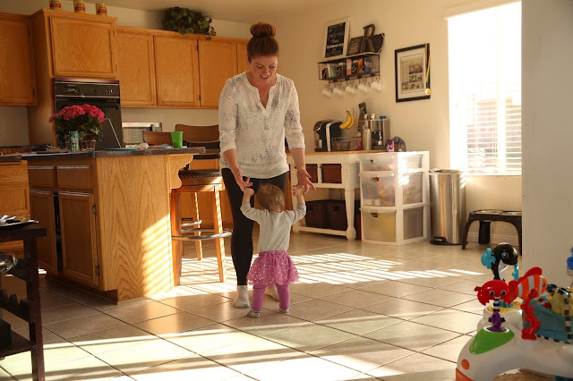 An open plan kitchen with a woman holding a toddler's hands