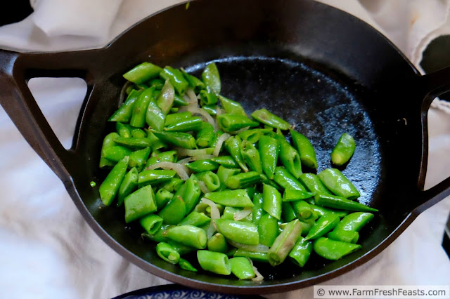 a Borough Furnace skillet with quickly cooked sugar snap peas and spring onions