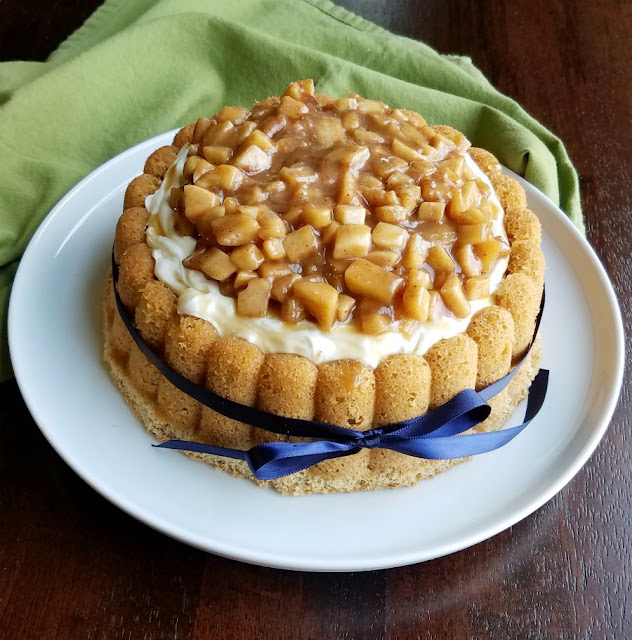 side view of cinnamon sponge cake baked into the shape of a Charlotte, topped with creamy filling and caramel apple chunks