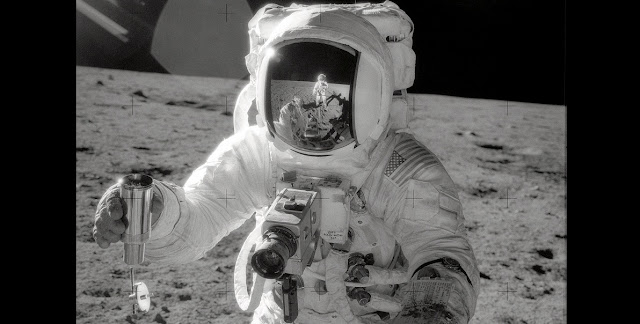 "Astronaut Alan L. Bean, Lunar Module pilot for the Apollo 12 lunar landing mission, holds a container filled with lunar soil collected while exploring the lunar surface. Astronaut Charles ""Pete"" Conrad Jr., commander, who took this picture, is reflected in the helmet visor. Credits: NASA"