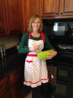 A Woman in a green shirt and a white/pink cooking apron with pink pockets