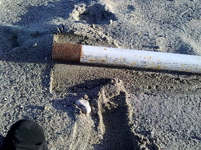 Image of rusty pole in the sand and foot print