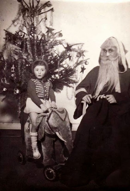 A little girl looks shocked sitting on a toy elephant by Santa. c.1950s. A Pleasant Christmas Story and other stories of Christmas Creepers. marchmatron.com