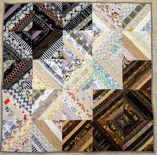 Scrap quilt of diagonal fabric strings in black, brown, and white.
