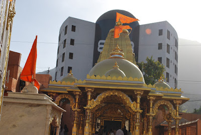 Notice the beautiful Shivling colored building in background