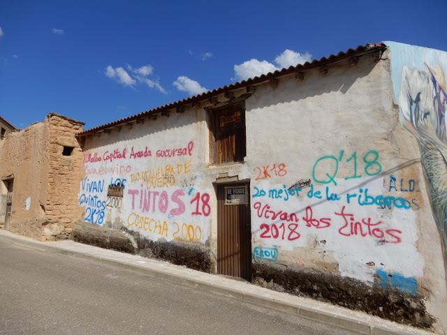 """Fachada blanca con múltiples pintadas alusivas y un cartel de """"se vende"""""""