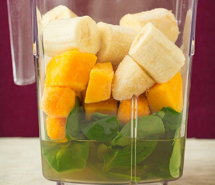 Banana, mangoes, and spinach in a blender