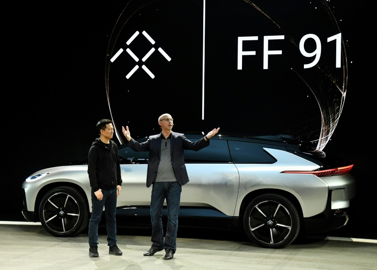 Jia Yueting (YT Jia,) (L) and executive vice president of engineering Nick Sampson unveil Faraday Future's FF 91 prototype electric crossover vehicle at CES 2017.