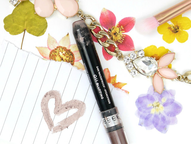 a silvery brown eye crayon in a black tube lay on a piece of paper. A heart is drawn next to it to show the exact shade.