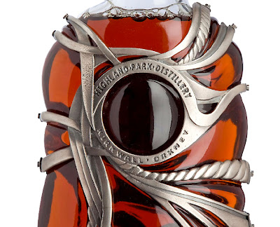 On the backside of the bottle, the medallion is replaced with a translucent glass cabochon