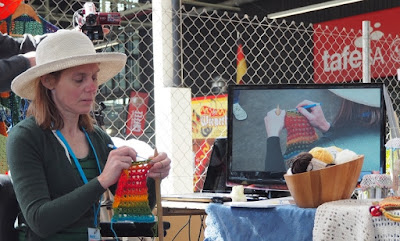 A side view of Jodie facing into the photograph. She is wearing a white hat and green long-sleeved cardigan. Jodie is crocheting a rainbow coloured scarf in broomstick lace. The camera is behind and above her head, catching the action from over her shoulder. The work is being displayed on the video monitor on the right hand side of the photo.