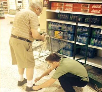 This employee decided to give an elderly gentleman a hand with tying his shoes.