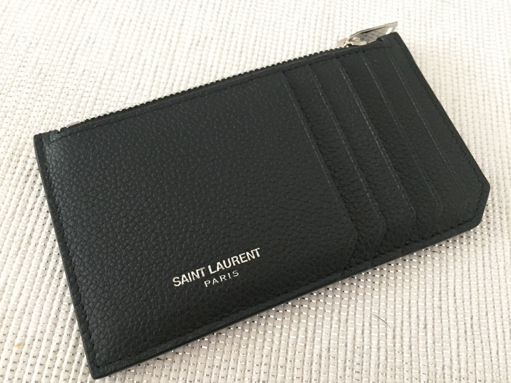 the card holder has a really nice grained black leather the front side with the 5 slots for your hards and the saint laurent paris logo in silver - Zip Card Holder