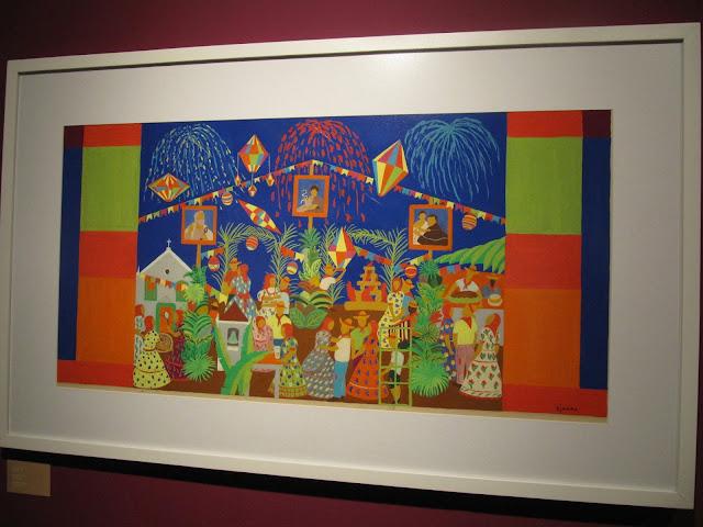 Quadro Festa Junina de Djanira. A obra retrata uma festa junina a noite com direito a balão de São João e imagens religiosas. Com uso de um traçado simples e geometrico.