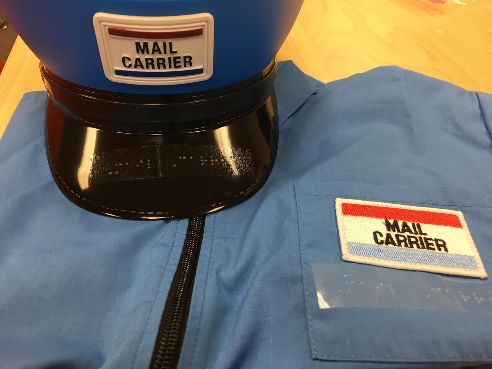 an image of the mail carrier dress up outfit with Braille label