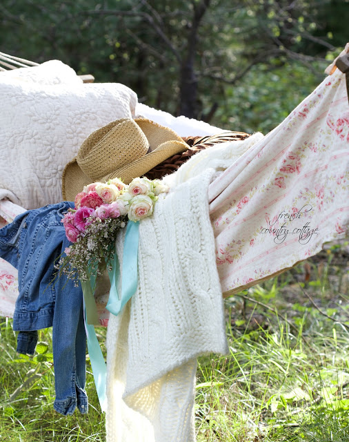 floral fabric, knit blanket and jean jacket on hammock
