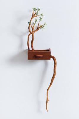 Escultura de madera de un cajón co ramas.