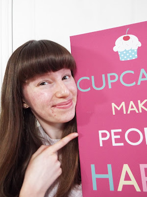 Smiling and pointing to 'Cupcakes Make People Happy' poster