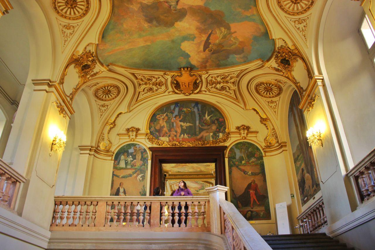 Uma escada no Capitólio de Toulouse, bastante chique e com pinturas nas paredes e no teto.