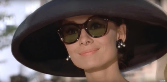 Audrey Hepburn is a big hat and oversized sunglasses