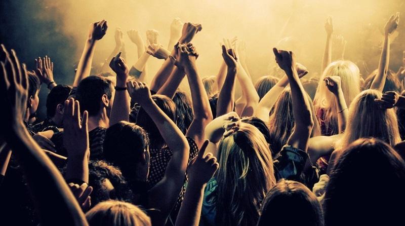 Jovens adorando a Deus em um culto especial com as mãos levandas