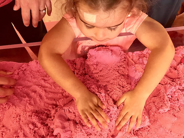 Toddler girl plays with pink kinetic sand