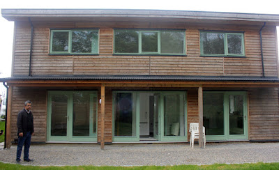 The South-facing front of a three bedroomed house with plenty of glazing to capture the sun's heat. Inside it falls onto a black, melamine-covered concrete floor to absorb the heat.