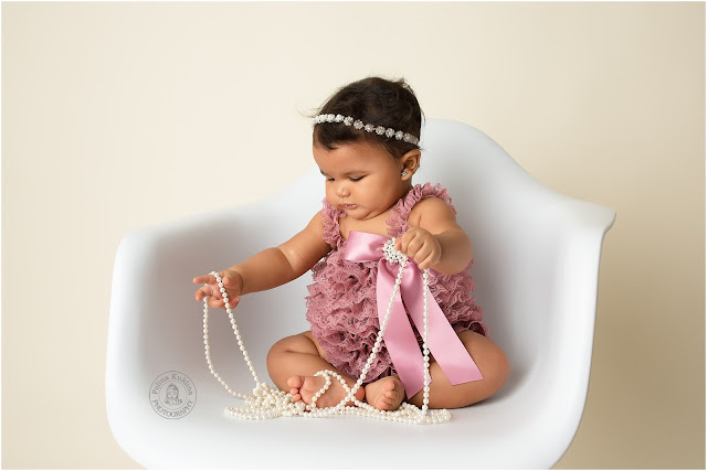 Beautiful 6-month baby girl playing with pearls