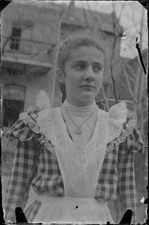 Foto einer junge Frau vor einem Haus - um 1900