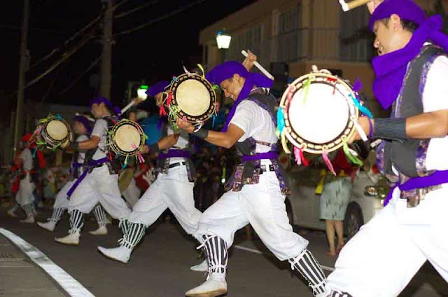 line of young men with drums, dance Eisa in street at night