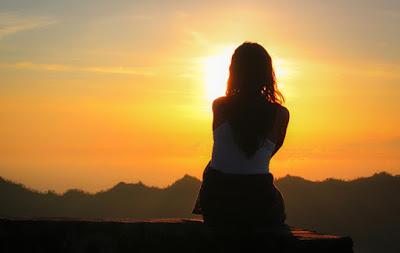 Mulher sentada observando o pôr do sol