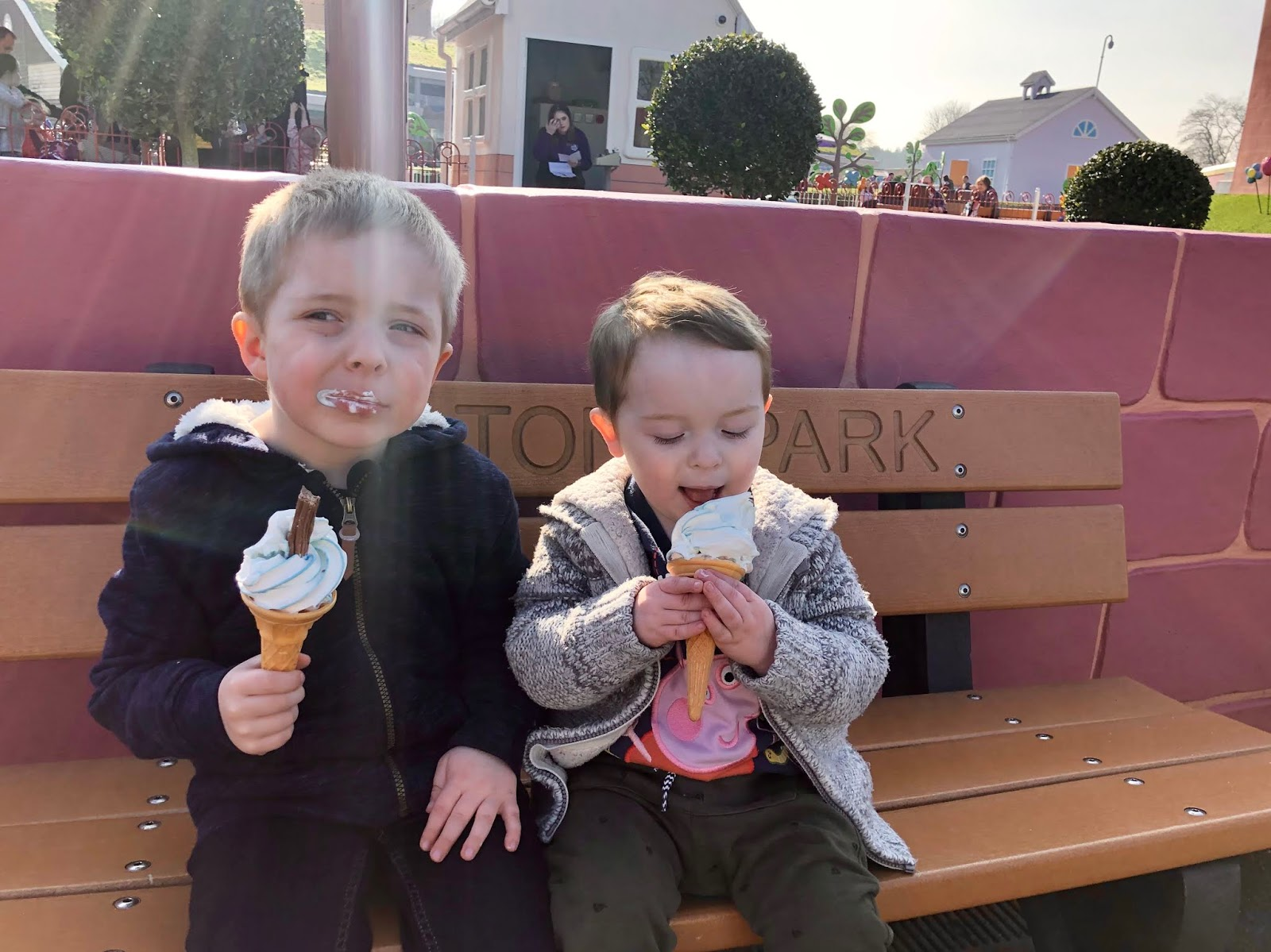 two young boys sitting on a bench and enjoying ice creams on a sunny day at peppa pig world paultons park