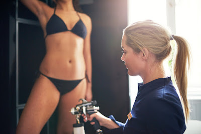 A female technician holding a spray tan gun. There's another woman in a bikini in the background (she is getting the solution applied on her).