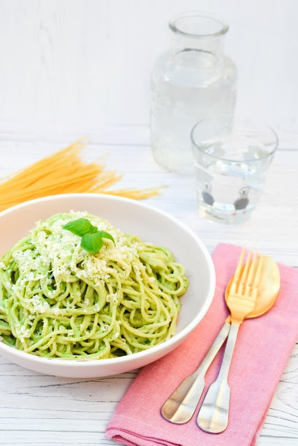 A bowl of  Kale and Cashew Pesto Spaghetti served with a glass of white wine